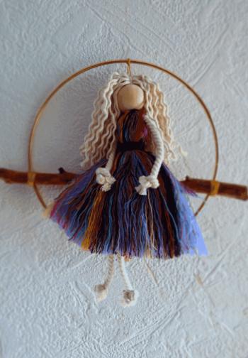 poupée réalisée avec restes de corde macramé, posée sur tige de bois et entourée d'un cercle métal